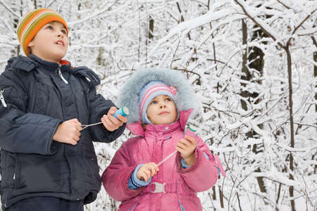 petard: cheerful boy and little girl with petard in hands in winter in wood Stock Photo