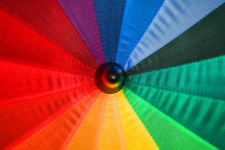 open multi-colored umbrella shot closeup, color segments photo