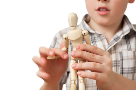 wooden mannequin: boy in checkered shirt is played by wooden little manikin isolated on white background, little manikin close up Stock Photo