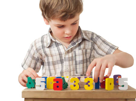 boys only: boy in checkered shirt displays wooden figures in form of numerals on table isolated on white background