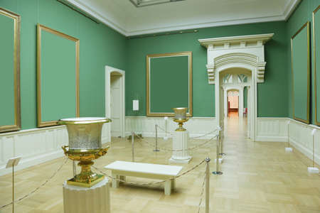 picture frames in green room of museum, white doors