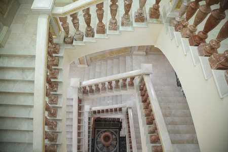white circular marble staircase with brown stand. shoot from top point. photo