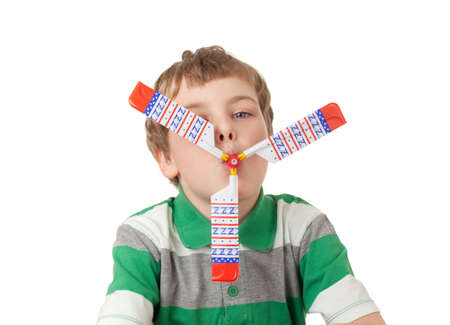 airscrew: boy in striped T-shirt with toy propeller in mouth  isolated on white background
