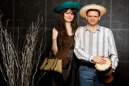 joven y bella mujer y el hombre sonriente en el sombrero y con el tambor Foto de archivo - 12136233