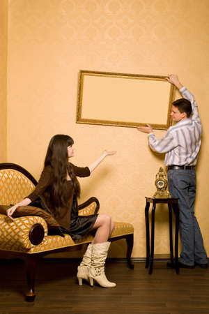 young beautiful woman sitting on sofa in room and smiling man hang up on wall picture in frame, looking against each other photo