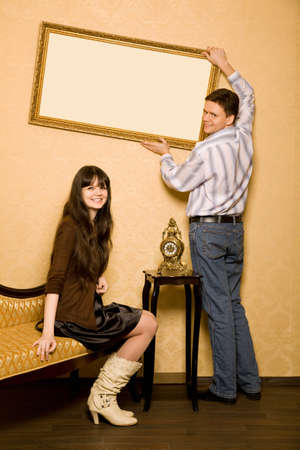 young beautiful woman sitting on sofa in room and smiling man hang up on wall picture in frame photo