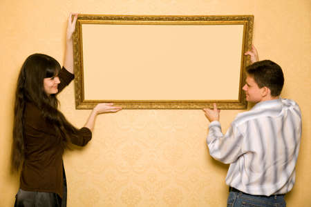 hang up: young beautiful woman and smiling man hang up on wall picture in frame, looking at picture