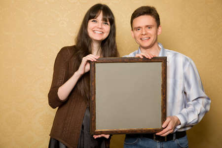 young beautiful woman and smiling man with picture in frame in hands  photo