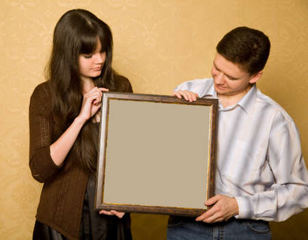 young beautiful woman and smiling man with picture in frame in hands, looking at picture photo
