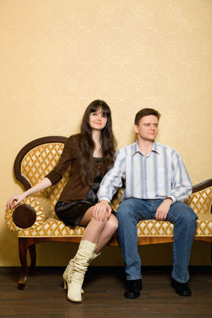 scruple: young beautiful woman and man sitting on sofa in room, man has put hand on knee to girl