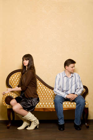 offence: young beautiful woman and young man sitting on sofa in room, have taken offence against each other