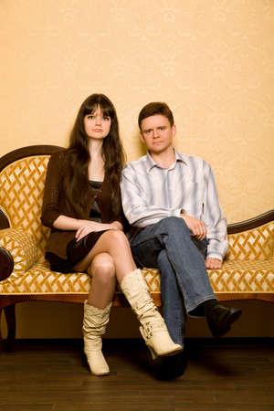 afecto: mujer joven y bella y joven sentado en el sof� en la habitaci�n, combinado las manos en el regazo
