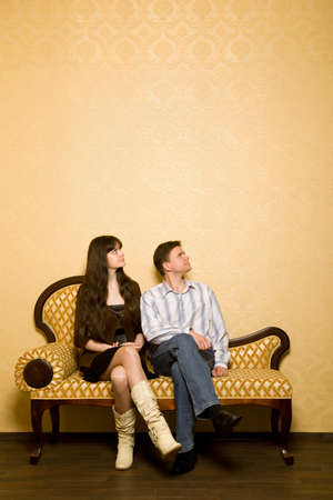 young beautiful woman and young man sitting on sofa in room, looking aside photo