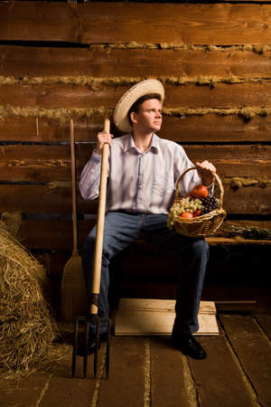 young man with pitchfork,with basket of fruit and in straw hat sitting on bench in wooden log hut photo