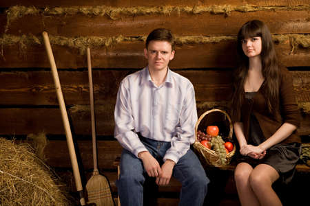 young man and beautiful woman near basket of fruit sitting on bench in wooden log hut photo