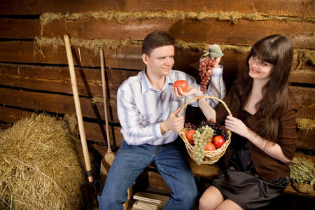 log basket: smiling man and young woman with basket of fruit sitting on bench in wooden log hut Stock Photo