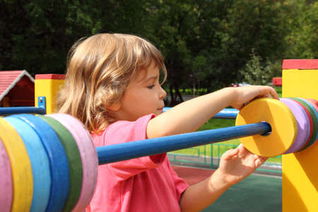 young girl playing at playground in summer sunny day, moves colour rings for mathematic counting  photo