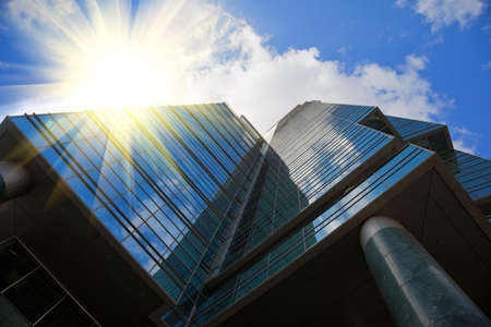 mirror office building in high tech style, blue sky with clouds reflected at here, rays of sun