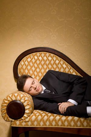 businessman in suit sleeping on sofa in room  photo