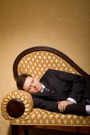 businessman in suit sleeping on sofa in room