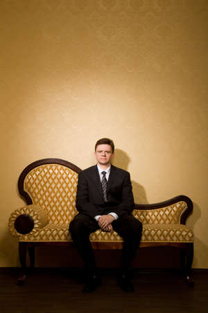 wellfare: businessman in suit sitting on sofa in room, �ombined hands together