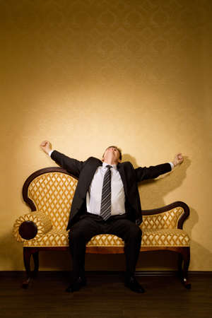 businessman in suit stretches after dream sitting on sofa in room  photo
