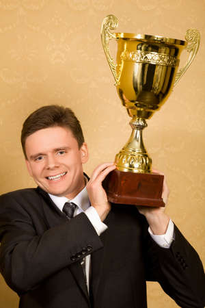 smiling businessman in suit with win cup in hand  photo