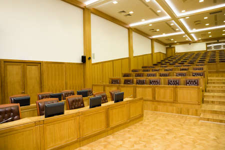 center table: Lateral part conference of halls with magnificent leather armchairs and wooden tables with microphones and monitors
