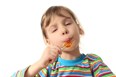licking in isolated: little girl licking orange lollipop, closed eyes, isolated on white