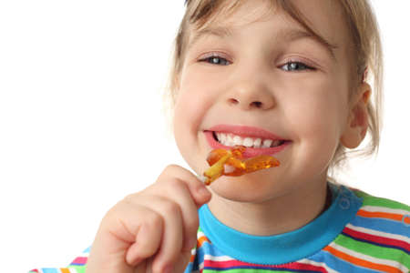 little girl eating orange lollipop, smiling and looking at camera, isolated on white photo