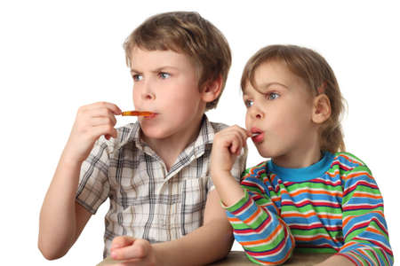 little boy and girl eating lollipops and looking at left side, half body, isolated on white Stock Photo - 12130781