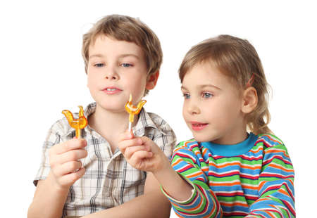 little boy and girl holding lollipops and looking on it, half body, isolated on white Stock Photo - 12130294