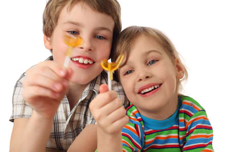 little boy and girl holding lollipops ,looking on it and laughing, half body, isolated on white photo
