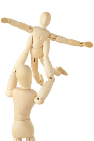 wooden mannequin: wooden figures of parent carring his child over his head, child aparting hands, half body, isolated on white Stock Photo