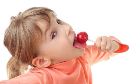 paletas de caramelo: Ni�a comiendo piruletas de color rojo, la mitad del cuerpo, mirando a c�mara, aislado en blanco Foto de archivo