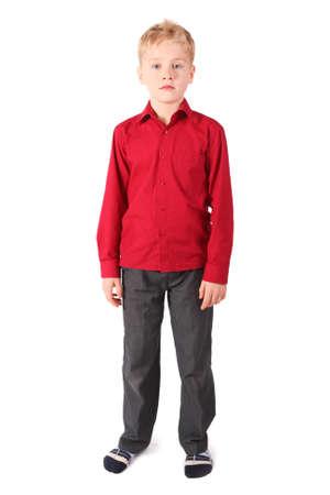 bambini pensierosi: un ragazzo giovane che indossa camicia rossa e pantaloni marroni in piedi da solo. isolata.
