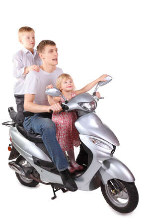 father and his son and daughter is sitting on      motorcycle. focus on fathers right leg. isolated. photo