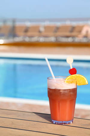 pool deck: cocktail with fruits in glass on ship deck floor near swimming pool