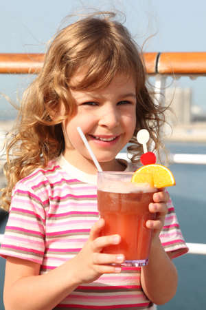 cool kids: little girl in shirt with pink stripes holding cocktail with fruits, smiling and looking at camera