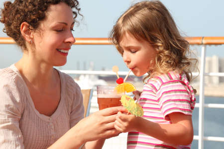 mother and daughter standing on cruise liner deck, mother holding cocktail in glass, daughter drinking it, horizontal photo