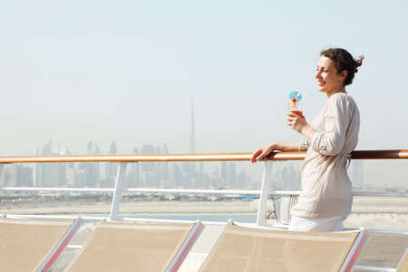 young beauty woman with cocktail standing on cruise liner deck, half body photo