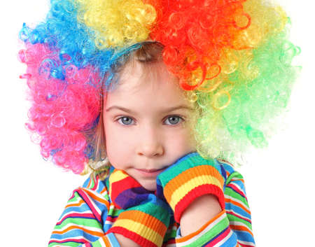 little girl in clown wig and multicolored gloves looking at camera, chin on hands, half body, isolated Stock Photo - 12130558