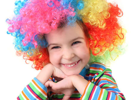 half body: little girl in clown wig smiling and looking at camera, chin on hands, half body, isolated