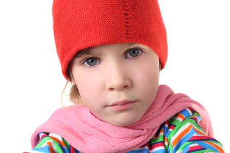 portrait of little serious girl in warm hat and scarf, half body, isolated on white photo