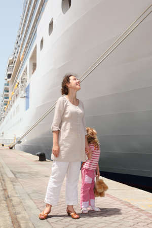 young mother and daughter standing in dock near big cruise liner and looking on it photo