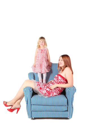 beautiful woman wearing dress is sitting on chair. her daughter is standing behind her. Stock Photo - 12130554