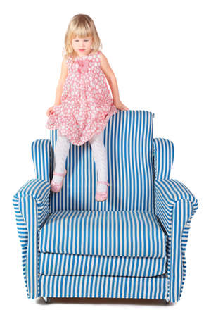 little girl wearing dress is sitting on back of striped chair. isolated. photo