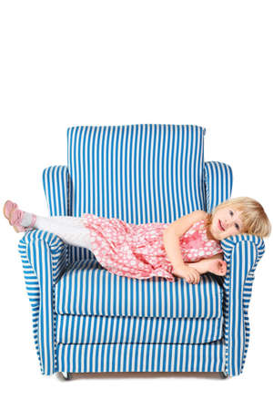 comfortable chair: little girl wearing dress and shoes is lying on comfortable chair. isolated.