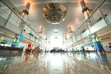 throughput: DUBAI - APRIL 19:  large hall with chairs, granite floor and columns in Dubai International Airport on April 19, 2010 in Dubai, UAE. The maximum throughput of the airport is 80 million passengers in a year.