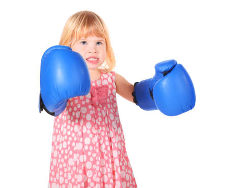 bared teeth: little girl with bared teeth wearing dress and boxers gloves is standing. isolated.